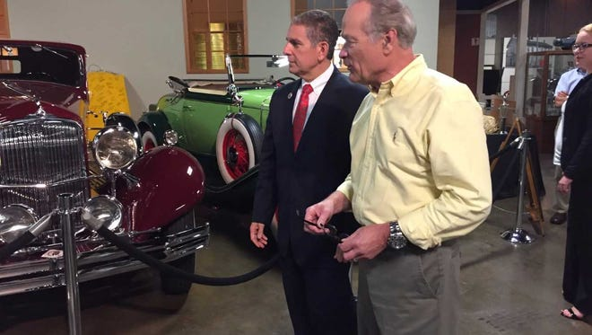Bill Adcock, executive director at the R. E. Olds Transportation Museum, gives Lansing Mayor Virg Bernero a brief tour of the museum on Oct. 3, 2017.