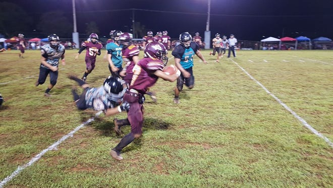 "Friar Running back Javian ""Chun"" Cruz just escapes a Southern Dolphins defender during FD's 36-6 win in IIAAG football Friday night at Hal's Angels Field in Dededo."