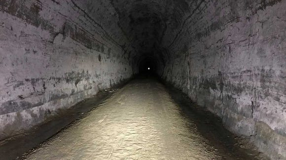 The inside of Tunnel 3 on the Elroy-Sparta State Trail is dark and damp, with water seeping through the earth.