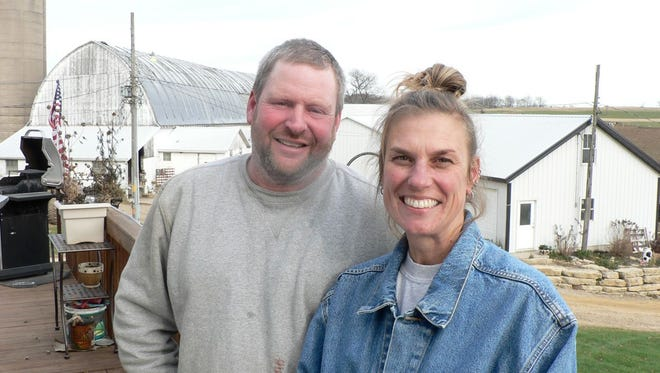Kurt and Kim Flannery on the deck of their house that overlooks the farm buildings.