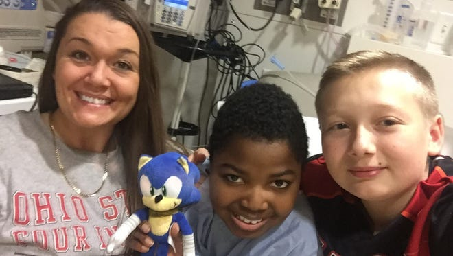 Annie Lykins and Vic Nera and her son Bryce Thompson are shown here at The Cleveland Clinic. Vic received a pancreas, liver and small intestine during a 16-hour surgery  on Nov. 20. Vic is a fourth grader at Malabar Intermediate School.