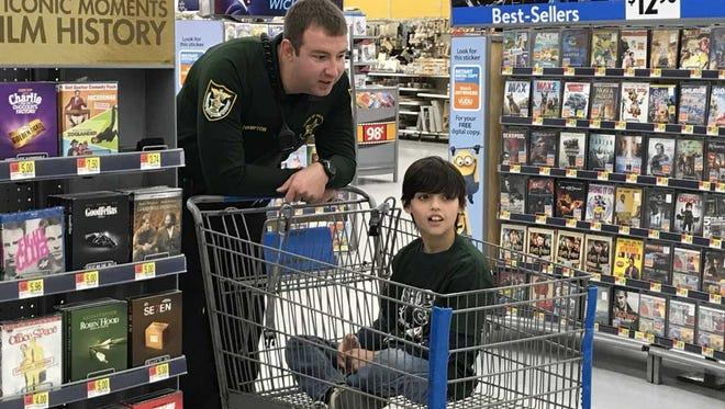 Escambia County Sheriff's Deputy Logan Hampton gives 9-year-old Logan a ride at Walmart