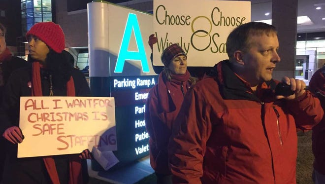 Jeff Breslin, RN and president of  Professional Employee Council of Sparrow Hospital, speaks during a picket rally Tuesday evening.