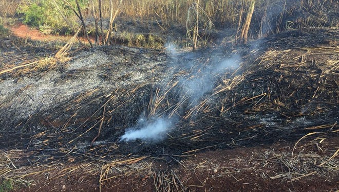 Ashes smolder after a grass fire was put out by the Guam Fire Department along Route 17 in Windward Hills on Dec. 26, 2017.