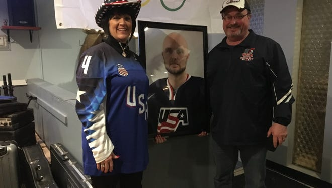 Chad Billins mother Teri and father Jason pose with a portrait of their son as they prepare to leave for the Winter Olympics.