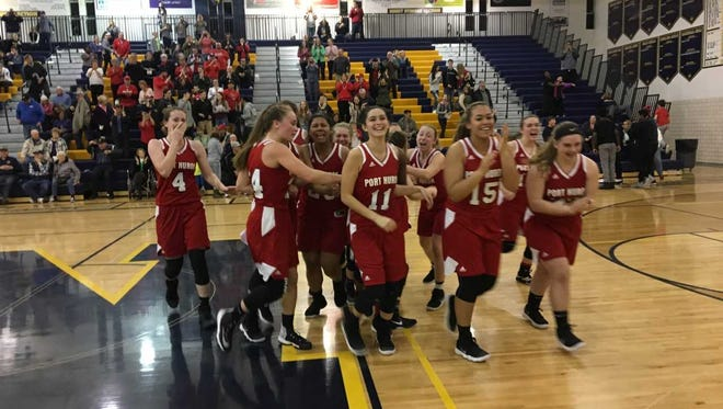 The Port Huron High School basketball team celebrates after defeating Port Huron Northern Monday.