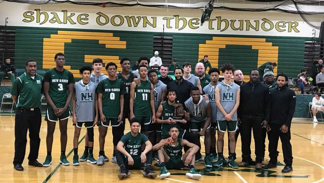 The New Haven High School boys basketball team poses for a photo after capturing a Class B district championship.