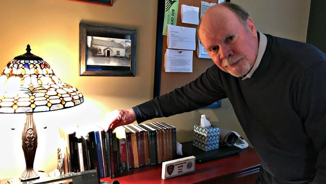 Knoxville resident Michael Grant looks at some of his novels lined up on an office bookcase.