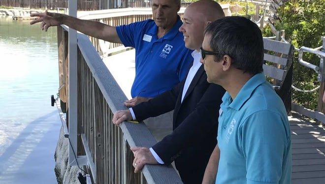 Mark Perry, executive director of the Florida Oceanographic Society, left, shows U.S. Rep. Brian Mast, R-Palm City, center, the society's gamefish lagoon Monday, April 30, as Zack Jud, the society's education director, right, looks on.