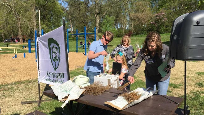 Participants in the Arbor Day Celebration hosted by the City of Henderson on Friday, April 27, pick out tree seedlings provided by the Henderson Rotary Club in honor of its centennial year in Henderson.