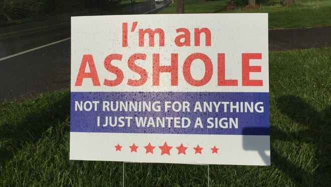 The sign pays homage to a late friend, and it satirizes political yard signs.