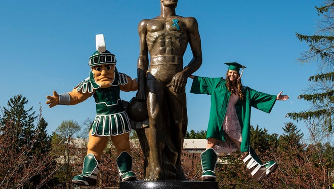 Three Sparty's hang out on Michigan State's campus on May 7, graduation day. Nicole Niemiec (right) played the role of Sparty the last three seasons. The Troy native failed her initial tryout during her freshman year, but after hours of studying and practice, fulfilled her goal of being the face of Michigan State University during her sophomore year.