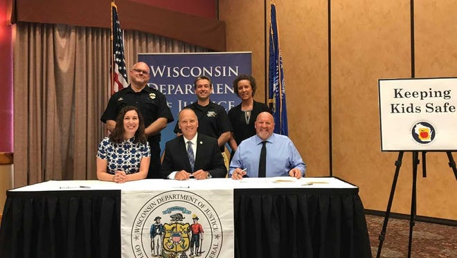 The Kettle Moraine School District will receive more than $190,000 in grant money from the state for school safety upgrades. Representatives of the district are pictured here with Wisconsin Attorney General Brad Schimel. They are (from left, back row) Delafield Police Chief Erik Kehl; Waukesha County Sheriff's Department deputy and school district resource officer James Soneberg; KM Middle School associate principal and school district co-director of safety Laura Lloyd, (front row) KM staff attorney and director of employee services Kristi Nelson Foy; Wisconsin Attorney General Brad Schimel; KM director of facilities and co-director of safety Dale Zabel.