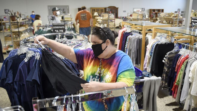 Christie Westbrook checks out some clothing at the opening of the relocated Catholic Social Services Thrift Store in Augusta, Monday morning July 6, 2020.