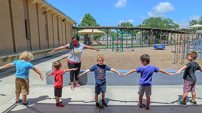 Ketterlinus Elementary School Summer Extended Day Program camp director Janet Bryant helps children practice social distancing before heading to lunch at the school in St. Augustine on Wednesday.