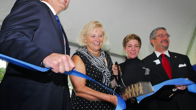 BlueWare CEO Rose Harr, left, joined business leaders in 2012 for a ribbon-cutting in Melbourne. The company soon vacated the building and Harr is facing criminal charges.