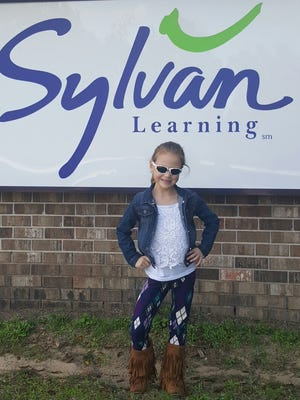 Josilyn Clenney, who receives tutoring at Sylvan Learning Center, poses in front of the location on Executive Plaza Road, which is under new ownership.