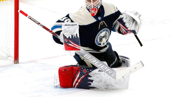 From Feb. 10, 2020, Columbus Blue Jackets goalie Elvis Merzlikins, of Latvia, makes a stop against the Tampa Bay Lightning during an NHL hockey game in Columbus, Ohio.  The Blue Jackets have signed rookie goaltender Merzlikins to a two-year contract worth a reported $8 million. The 26-year-old Latvian became a fan favorite while successfully filling in for an injured Joonas Korpisalo in the second half of the season.