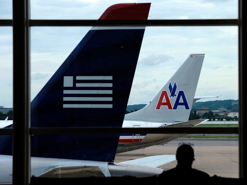 An American Airlines plane and a US Airways plane are  parked at Washington's Ronald Reagan National Airport on August 13.