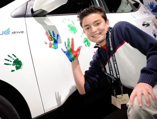A boy shows off his handprint as part of Hyundai's Hope on Wheels campaign in support of research for pediatric cancer