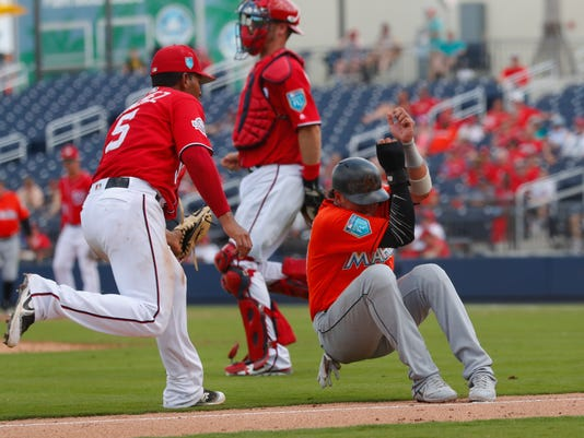 Miami Marlins' Starlin Castro (13) is tagged out by Washington Nationals third baseman Adrian Sanchez (5) after being caught in a rundown between third and home on a Lewis Brinson ground ball in the fifth inning of a spring training baseball game Tuesday, March 20, 2018, in West Palm Beach, Fla. (AP Photo/John Bazemore)