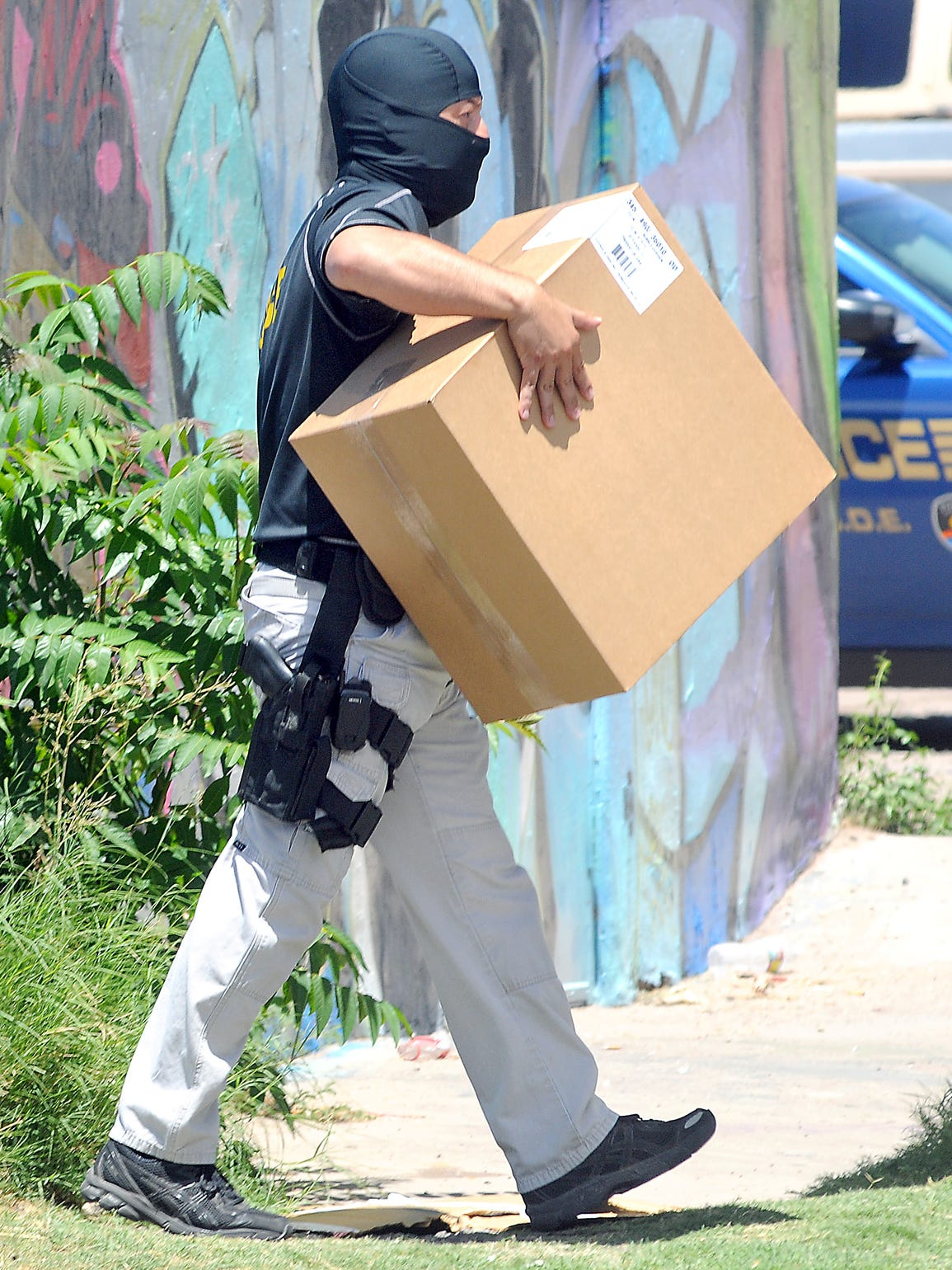 A masked DEA agent carries evidence out of Phat Glass,