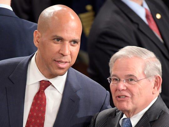 Sen. Corey Booker (D-NJ) and Sen. Robert  Menendez (D-NJ) speak before President Donald Trump addresses a joint session of Congress at the U.S. Capitol.
