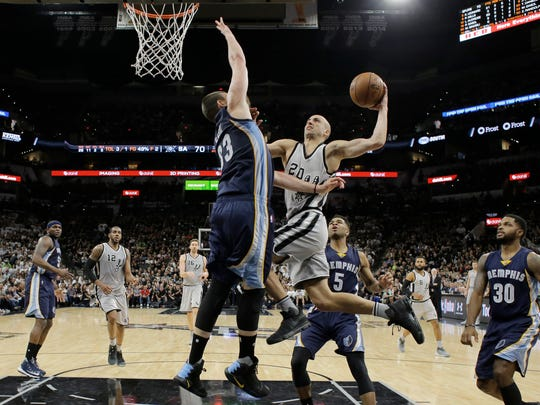 San Antonio Spurs guard Manu Ginobili (20) drives to the basket against Memphis Grizzlies center Marc Gasol (33) during the second half in Game 1 of a first-round NBA basketball playoff series, Saturday, April 15, 2017, in San Antonio. San Antonio won 111-82.