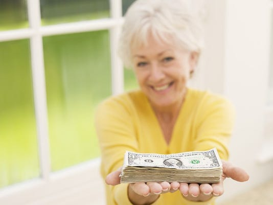 old-woman-holding-pile-of-money_large.jpg