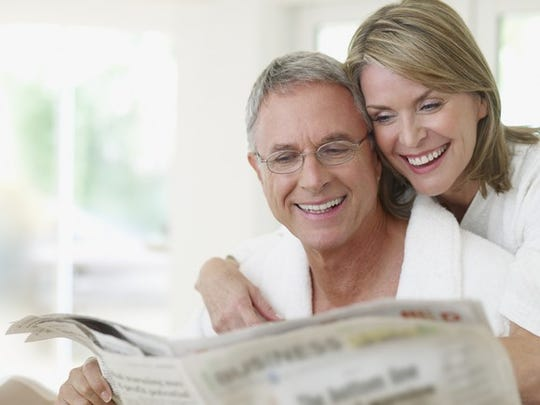 Smiling older couple reading a newspaper