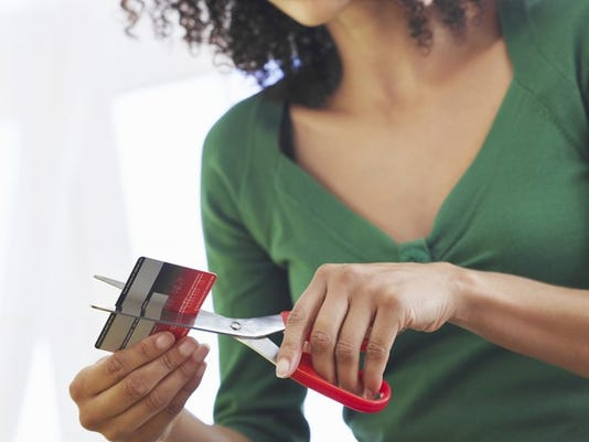 young-woman-cutting-credit-card-in-half-with-scissors-debt-poc_large.jpg