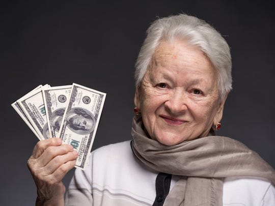 A senior woman holding up a fanned pile of hundred dollar bills in her right hand.