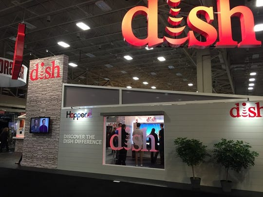 Booth at convention center with DISH setup, including wall and large-screen TV.