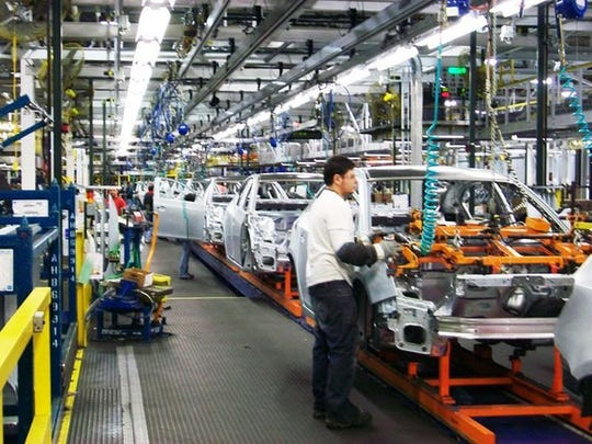 Workers on an automotive assembly line tend to partially-assembled Chevrolet Cruze sedans.