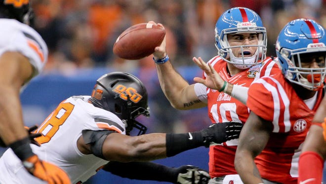 Quarterback Chad Kelly (10) is pressured on a throw by Oklahoma State's Emmanuel Ogbah (38) in the Sugar Bowl. Kelly could be one of three Ole Miss players taken in the first round of next year's draft.