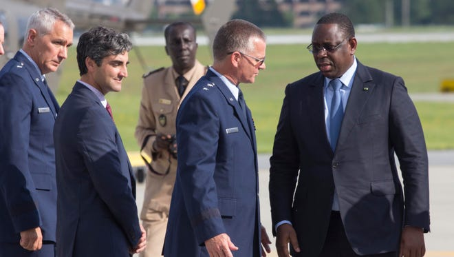 Senegal President Macky Sall, right, is greeted by Adjutant Gen. Steven Cray of the Vermont National Guard, second from right, as Burlington Mayor Miro Weinberger, second from left, and Gen. Richard Harris, left, of the Vermont Army National Guard after arriving in Vermont on Thursday