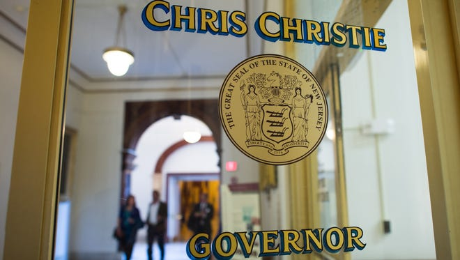 People walk near the office of Governor Chris Christie inside the New Jersey State House in Trenton, New Jersey, U.S., on Tuesday,  March 11, 2014. New Jersey's pension system is underfunded by $52 billion after a decade of expanded benefits and missed payments, Governor Chris Christie said last month. Photographer: Ron Antonelli/Bloomberg ORG XMIT: 478664857