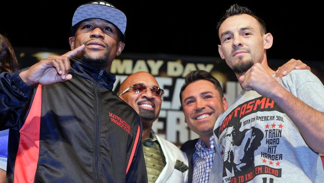 Boxers Floyd Mayweather Jr., left, and Robert Guerrero, right, pose for photographers with Mayweather's adviser, Leonard Ellerbe, second from left, and Oscar De La Hoya, during a news conference  May 1, 2013, in Las Vegas.