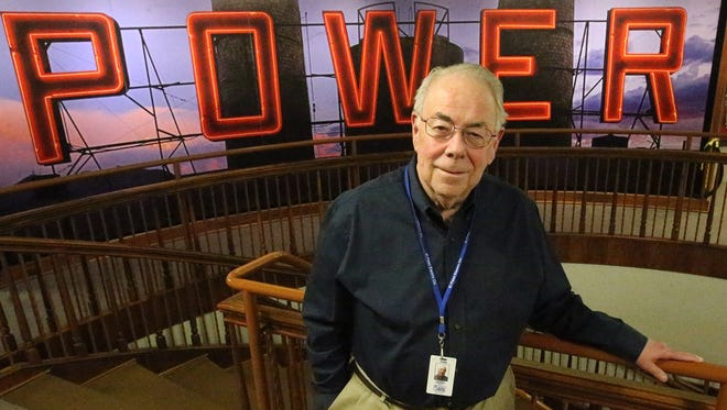 El Paso Electric CEO Tom Shockley stands in front of a photo of the company's Rio Grande power plant sign inside the company's headquarters. He will retire Dec. 15.