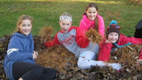 St. Peter Middle School students take a break from raking leaves during the United Way of Portage County's Make a Difference Day Rake-A-Thon on Oct. 25.