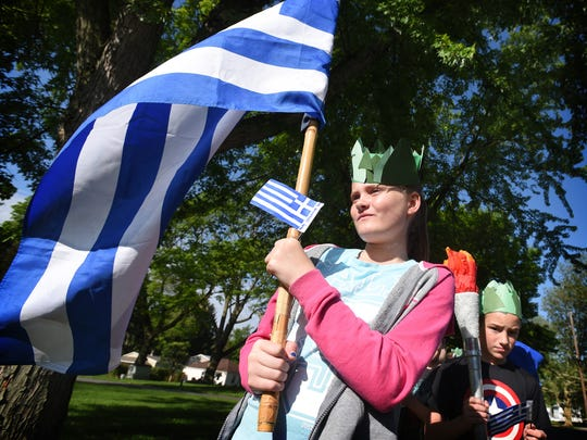 Serenity Webster carries the flag of Australia during Annville Elementary School's Olympic march Thursday, May 19, 2016, to Annville-Cleona High School for the elementary school's field day.