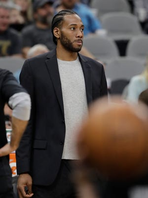 San Antonio Spurs forward Kawhi Leonard, waiting to return from injury, wears street cloths as he watches from the bench.