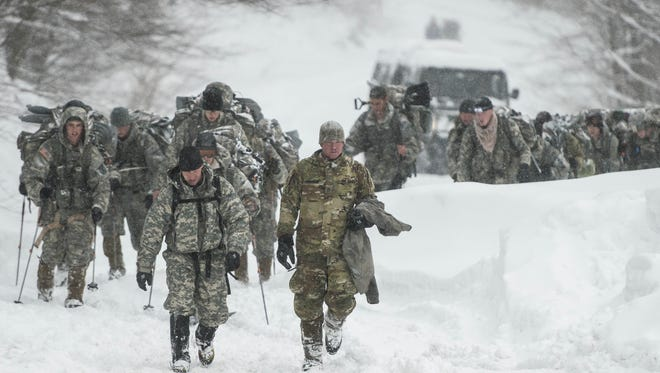 Vermont National Guard soldiers on a training exercise emerge from a closed section on Vermont 108 in Cambridge, Vt., just below Smuggers Notch on Wednesday night, March 14, 2018, after six soldiers were swept approximately 300 meters by an avalanche.