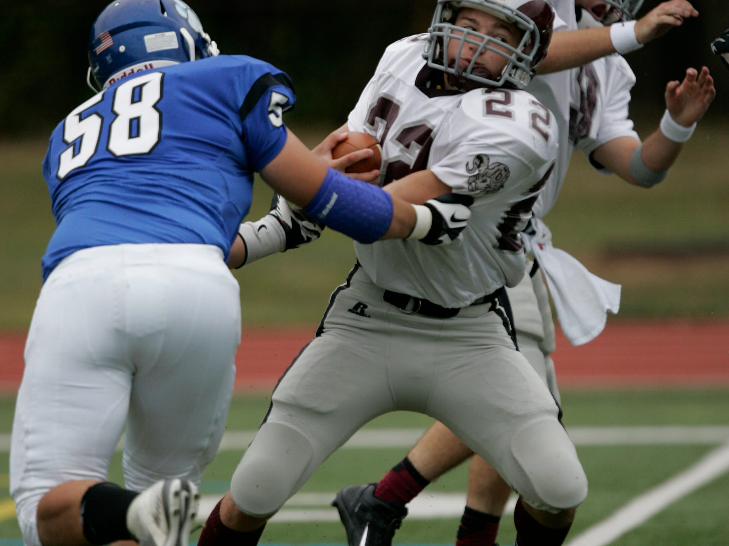 Metuchen high school football player #58 Robby Gilman tries to strip the ball from South River high school player #22 Mario Nigroin the first half against Metuchen high in a game at Metuchen high school Saturday September 13, 2014 photo by Ed Pagliarini EST 0914 FB South River-Metuchen