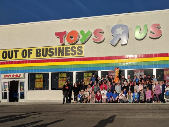 Toys R Us mascot Geoffrey the Giraffe poses with employees