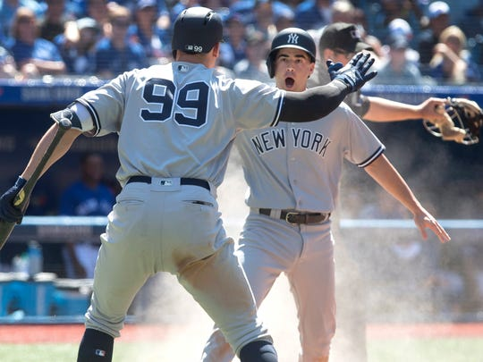 New York Yankees' Aaron Judge, left, greets Tyler Wade, right, who scores against the Toronto Blue Jays in the 10th inning.