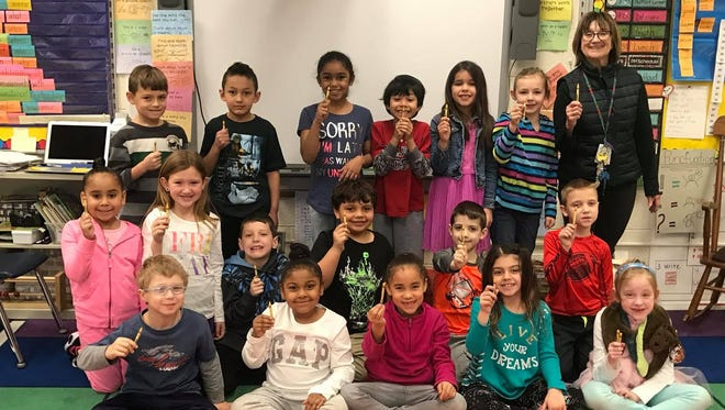 Kathy Glick and her first grade class hold up dandelion crayons, since Crayola is retiring the color.