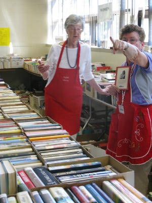 Susan Bocchetti (on the right) points to the location of a category to Marjorie Salmon. Both are volunteers at the Penfield Library's 2015 Used Book Sale.