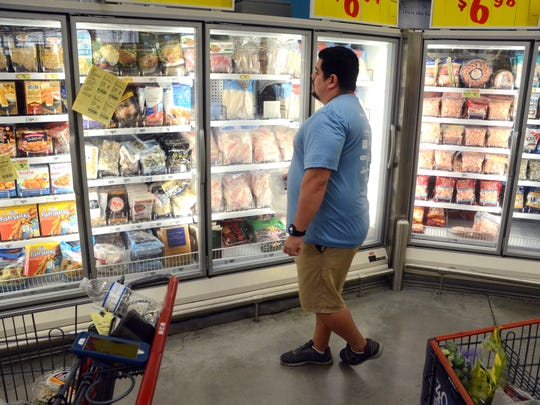 Corpus Christi Slim Down Showdown contestant Rocky Bloom looks at the frozen seafood section during a pantry makeover at the H-E-B Plus! on Saratoga Boulevard in late January.