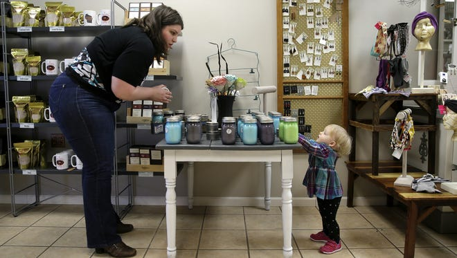 Jennifer Theuerkauf organizes candles while her youngest daughter, Sybil, helps at The Fine Fox in Neenah.  Wisconsin